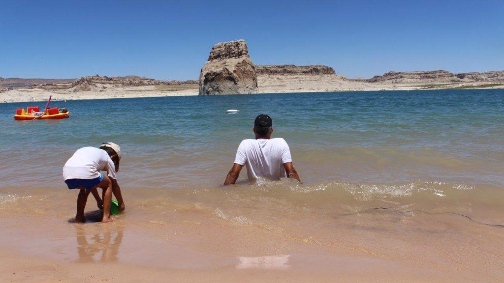 While the son enjoy the water and the sand, the father take the time to relax inside Lake Powell, at Glenn Canyon National Recreational Area